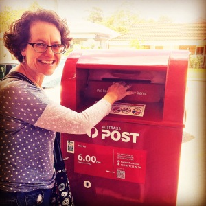 Photo of Rebecca Newman in a spotted shirt posting a letter into a red post box.